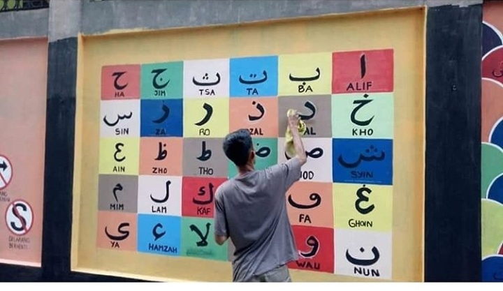 Para pemuda ini membuat mural sebagai media pembelajaran