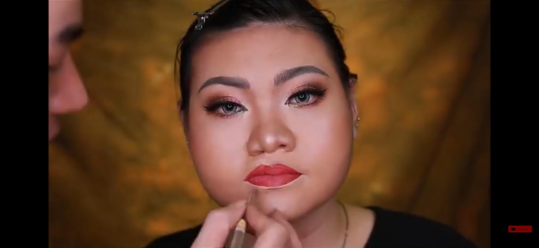 Trang memakai lipstick