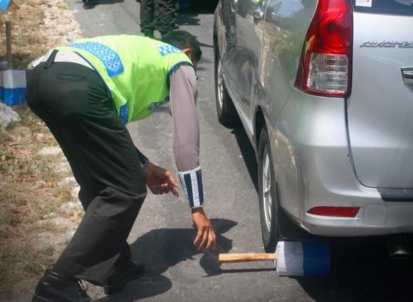 Satu tim polisi ini tugasnya mengganjal ban mobil pada tanjakan! Salut