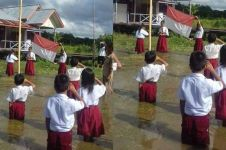 Siswa-siswa SD ini khidmat upacara bendera di tengah banjir
