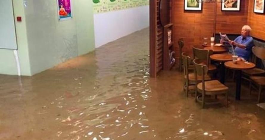 Tak peduli ada banjir besar, kakek ini tetap santai menyeruput kopi