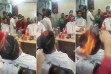 Tukang cukur ini potong rambut pakai api, kamu berani coba?
