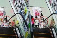 Naik eskalator sambil nengok bawah, gadis ini nyaris kehilangan kepala