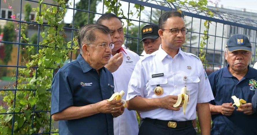 Tunjukkan nggak bau lagi, Anies dan JK makan pisang di tepi Kali Item