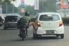 Viral pengendara motor dorong mobil, dijuluki kaki terkuat di bumi