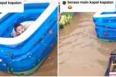 Viral aksi kocak orang tua hibur anaknya kala banjir mengepung