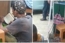 Viral pedagang bertato tunggu pembeli sambil mengaji, menyentuh banget